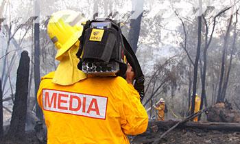 A camera operator filming a hazard reduction burn